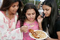 Asian Culture Festival, Indian Hindu teen girls, eat Thai food, cell phone. Fruit and Spice Park. Homestead. Florida. USA