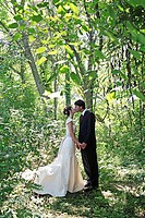Newlywed couple kissing in forest