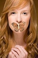 Butterfly covering womans mouth