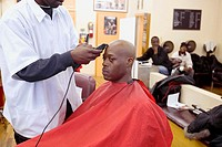 USA. New York City, Harlem. Man getting head shaved at barber shop.