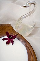 Spa elements, koa bowl filled with milk, garnished with an orchid, with glass swan