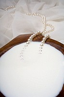 Spa elements, koa bowl filled with milk, garnished with a pearl necklace
