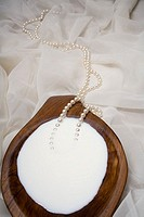Spa elements, koa bowl filled with milk, garnished with a pearl necklace (thumbnail)