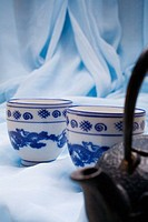 Spa elements, Oriental teacups and cast iron tea kettle nestled upon blue cloth