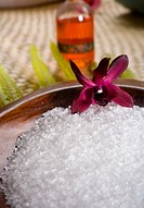 Spa elements, koa bowl filled with raw salt, garnished with orchid, leaf and bath oil blurred in background