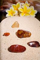Spa elements, polished rocks and plumerias in a bowl filled with sand