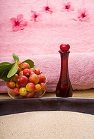 Spa elements, a bowl filled with sand and pink towel, bowl of fruit, flowers and glass bottle