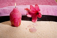 Spa elements, Budha head candle and pink stones in a bowl of sand, with pink hibiscus and pink towel