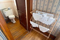 Underwear drying on a wooden rack, next to the bathroom
