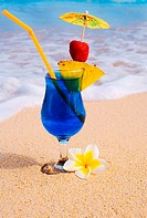 A Blue Hawaii tropical cocktail on the beach, wave washing on the sand