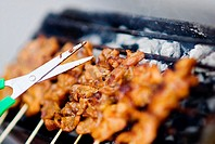Thailand, Bangkok, unusual delicacies found at street vendor food stalls, skewers of chicken on grill with scissors poised above