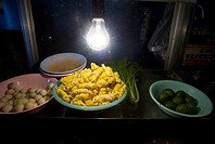 Thailand, Bangkok, unusual delicacies found at street vendor food stalls, bowl of rolled pastries lit by a single lightbulb