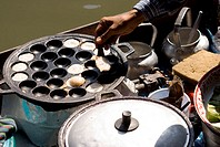 Thailand, Bangkok, Close-up of hands spooning an exotic Thai food from a special skillet at the floating market