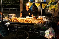 Thailand, Bangkok, vendor cooking and selling food from a cart on the street