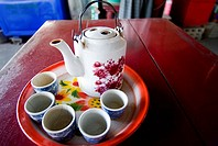 Thailand, Bangkok, Teapot and teacups on a platter on a tabletop at a local restaurant