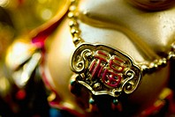 Golden figurine depicting a portly Chinese man, focus on icon resting on his belly
