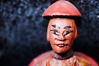 Close-up of an asian man figurine painted red