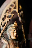 Close-up of a Buddha sculpture on a carved throne
