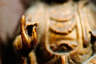 Close-up of a Buddha sculpture in meditation pose with fingers in 'ohm' position
