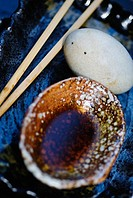 Chopsticks, a small dish and an egg on a textured blue plate