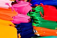 Thailand, Bangkok, Wat Ratchanadt Amulet Market, brightly colored cloth satchels