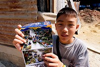 Thailand, Bangkok, Damnoen Saduak Floating Market, young boy selling postcards