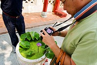 Thailand, Bangkok, Summer Palace at Bang Na, Japanese tourist photographing flower