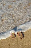 Woven top slippers, with red Hawaiian print edging, on sand, sea foam washing over