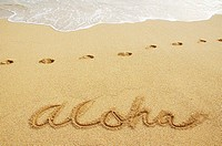 Aloha written in sand with footprints and wave wash