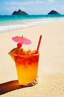 A mai tai garnished with pinapple and a cherry, sitting in the sand on the beach