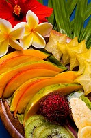 Studio shot pf a variety of tropical fruit sliced on a platter, with flowers