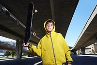 Teenager in Hooded Jacket Holding Skateboard