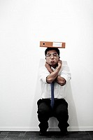 Businessman Squatting and Balancing a Binder on His Head