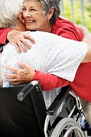 Senior Woman Hugging Senior Man in Wheelchair