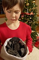 Boy holding stocking full of coal