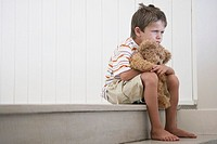 Sad young boy with a teddy bear
