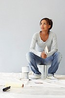 Woman sitting on paint can, thinking