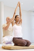 Man and woman doing yoga (thumbnail)
