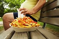 Overweight Man on Bench Next to French Fries