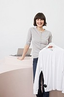 Young store clerk holding t-shirt on hanger