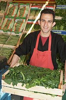 Grocer carrying a crate of spinach