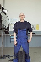 Mechanic standing with tire between legs