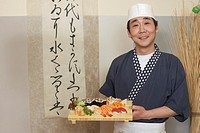 Sushi chef holding tray of sushi