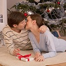 Couple kissing in front of the Christmas tree