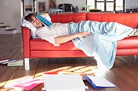 Man sleeping on couch with book