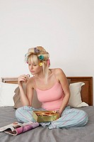 Woman in hair curlers reading and eating chocolates