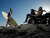 Couple with Trike and Surfboard on Beach