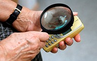 Elderly woman with cell phone and magnifying glass