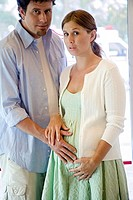 Mid adult man touching the abdomen of a pregnant young woman