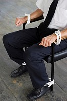 Businessman being tied to a chair